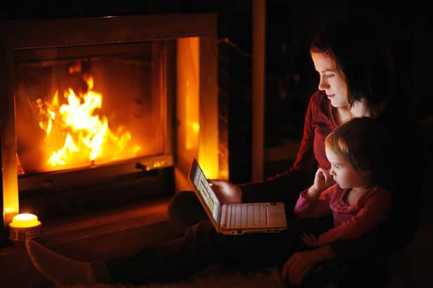 Young mother and daughter by a fireplace with a laptop